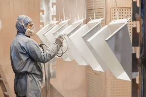Employee Painting shrouds for a mining truck